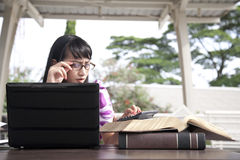 Young beautiful woman works outdoor. Young asian woman with glasses working on her laptop outdoor Royalty Free Stock Photography
