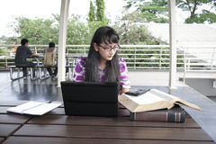 Young beautiful woman works outdoor. Young asian woman with glasses working on her laptop outdoor Royalty Free Stock Photo