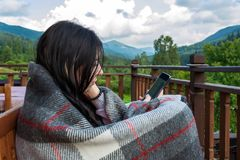 Young, beautiful woman wrapped in plaid looking at phone on mountain background stock images