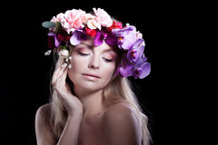 Young beautiful woman in wreath of flowers holds Stock Image