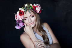 Young beautiful woman in wreath of flowers holds Royalty Free Stock Image