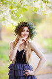 Young beautiful woman in a wreath of flowers outdoors Royalty Free Stock Image