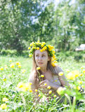 The young beautiful woman in a wreath from Globeflower in  field Royalty Free Stock Image