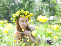 The young beautiful woman in a wreath from Globeflower in  field Royalty Free Stock Photos