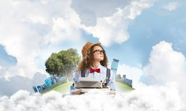 Creative inspiration of young female writer. Young and beautiful woman writer in hat and eyeglasses using typing machine while sitting at the table with Stock Image