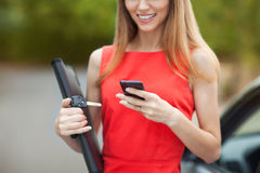 Young beautiful woman writes an SMS. To your mobile phone Stock Photos