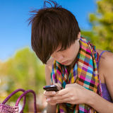 Young beautiful woman writes an SMS Royalty Free Stock Image