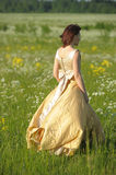 Young beautiful woman in a yellow  dress in the field Royalty Free Stock Images