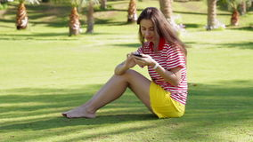 Young beautiful woman in yellow dress sitting on grass in summer city park with phone stock video