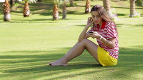 Young beautiful woman in yellow dress sitting on grass in summer city park with phone stock video footage