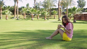 Young beautiful woman in yellow dress sitting on grass in summer city park with phone stock footage