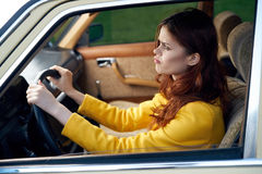 Young beautiful woman in a yellow sweater is driving a car in the city Royalty Free Stock Photo