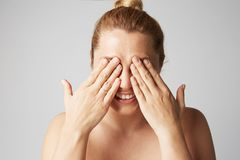 Young beautiful women with blonde hair fixed behind, big eyes, and naked shoulders smiling and closes her eyes with two royalty free stock photo