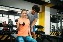 Young beautiful woman doing exercises with personal trainer Royalty Free Stock Images