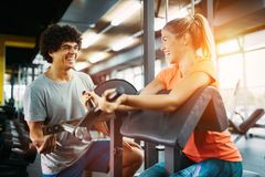 Young beautiful woman doing exercises with personal trainer Royalty Free Stock Photography