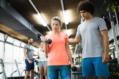 Young beautiful woman doing exercises with personal trainer stock images
