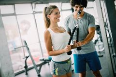 Young beautiful woman doing exercises with personal trainer stock image