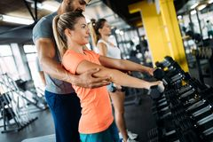 Young beautiful woman doing exercises with personal trainer. Young beautiful women doing exercises with personal trainer in gym Royalty Free Stock Photo