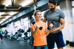 Young beautiful woman doing exercises with personal trainer. Young beautiful women doing exercises with personal trainer in gym Royalty Free Stock Image