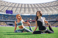 Young beautiful women doing yoga in morning at the stadium. Two young yoga female in yoga pose Stock Images