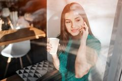 Young beautiful woman drinking coffee at cafe bar. Female model Young using smartphone at cafe stock photos
