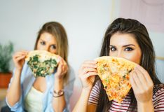 Young beautiful women eating slices of taste Italian pizza at home - Happy pretty sisters covering their faces with fast food stock photo