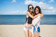 Young beautiful women embracing each other on beach royalty free stock photos