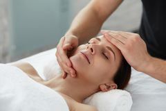 Professional massage therapist is treating a female patient in apartment. royalty free stock photos