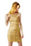 The young beautiful women in a golden dress. Isolation on a whit Stock Photo