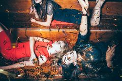 Young beautiful women having fun on party lying on the floor in. Beautiful young women having fun on crazy party lying on the floor in confetti. New year royalty free stock photography