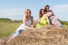 Young beautiful women on hay Stock Image