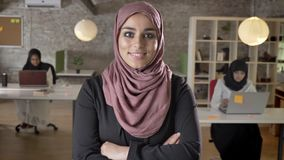 Young beautiful women in hijab with crossed hands standing in modern office, happy and smiling, two muslim womens. Working on laptop stock video footage