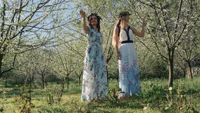 Young beautiful women in long dresses between spring blossom trees. Young beautiful caucasian women in long dresses in bay leaf wreath standing dreamily in stock video