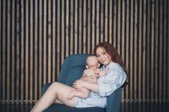 Young beautiful woman hugs her newborn baby royalty free stock photo