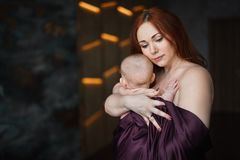 Young beautiful woman hugs her newborn baby royalty free stock image