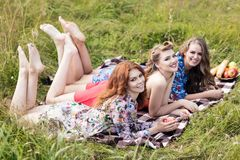 Young beautiful women lying on plaid in summer park. stock images