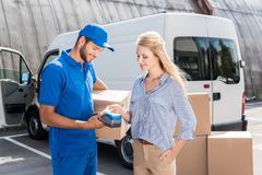 Woman paying for delivery with card. Young beautiful women paying for delivery with card Royalty Free Stock Image