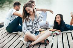 Young beautiful woman relaxing by river in company of friends royalty free stock images