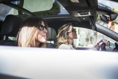 Two women singing in the car. Young and beautiful women singing and dancing to the rhythm of music in their car royalty free stock photos