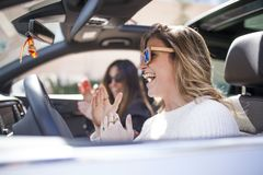 Two women singing in the car. Young and beautiful women singing and dancing to the rhythm of music in their car stock photo