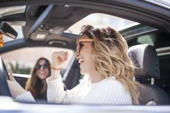 Two women singing in the car. Young and beautiful women singing and dancing to the rhythm of music in their car royalty free stock images