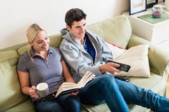 Young woman reading a book next to her boyfriend watching TV. Young beautiful women smiling while reading a book next to her boyfriend watching TV on the sofa at stock images