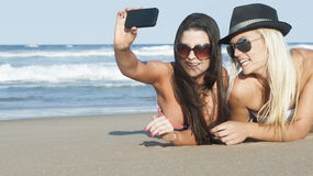 Young beautiful women taking photos on beach. With cellphone camera Stock Photo
