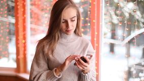 Young beautiful women texting or using internet on the smartphone. Bokeh background. Winter stock footage