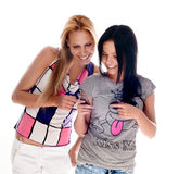 Young beautiful women using the cellphone. To send and receive sms Stock Photography