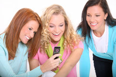 Young beautiful women using a cellphone. Beautiful teenage girls using a cellphone Royalty Free Stock Image