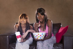 Young beautiful women watching television with popcorn. Young beautiful women watching television while eating popcorn Royalty Free Stock Photography