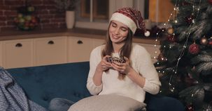 Young beautiful women wearing santas hat sitting on a sofa at cosy Christmas background holding small present box stock footage