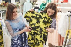 Young beautiful women at the weekly cloth market - Best friends sharing free time having fun and shopping stock photography