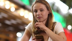 Young beautiful worried girl with a phone looking to camera and being tense. stock footage